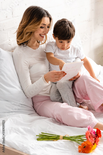happy mother holding adorable son and mothers day card while sitting in bed near flowers