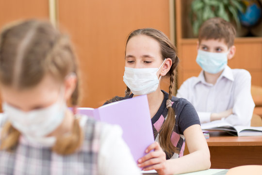 Pupils wearing protection mask to prevent virus during lesson in classroom in school