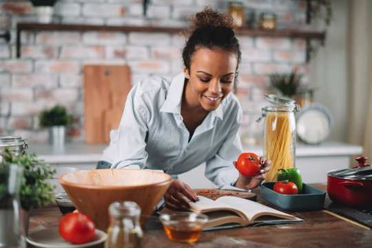Young woman in kitchen. Beautiful mixed race woman following recipe and cooking.