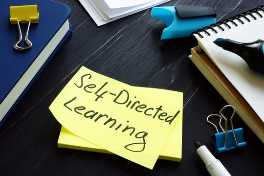Self-directed learning or education concept. Book and notes with pen.