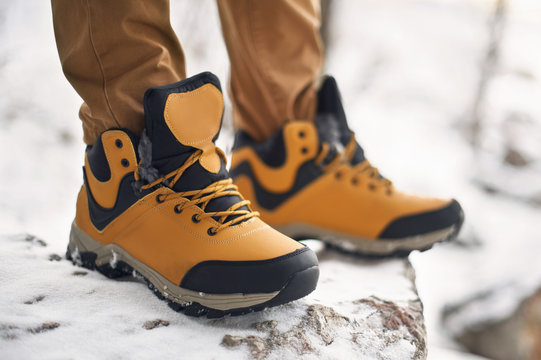 Hiking or trekking shoes on snow close up shot. Technical outdoor boots low angle view. Mountaineering or climbing winter shoes detailed product photo.