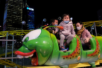 Visitors wear masks to prevent an outbreak of a coronavirus as they enjoy a ride at a carnival in Hong Kong