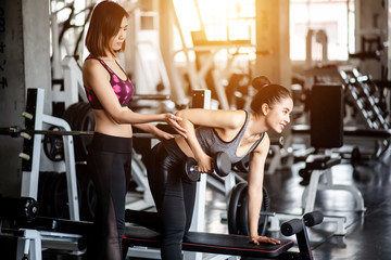 Young healthy woman lifting dumbbells in the gym with personal trainer
