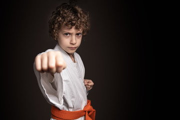 Karate kid fist on dark background. Caucasian boy keeping a karate position wearing the kimono and the orange belt