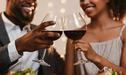 Close up of african couple toasting with red wine