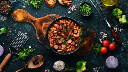 Beans with sausages in tomato sauce on a black plate.  Top view. Free space for your text.
