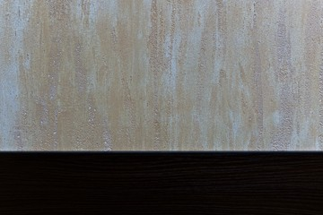 Plastered light beige with a pearly glitter background with a dark wooden stripe at the bottom.