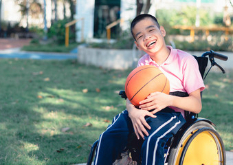 Disabled child on wheelchair is playing basketball on the lawn in front of the house like other people, Lifestyle of special child,Life in the education age of children, Happy disability kid concept.