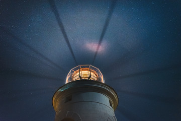 the sea lighthouse shines at night with bright rays of light against the background of the starry sky
