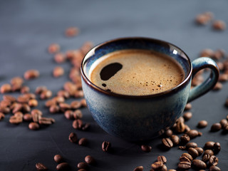 Blue Cup of fresh hot espresso coffee on a dark table with coffee beans
