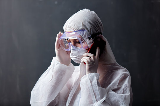 medic woman wearing protective clothing against the virus is using mobilephone for publicity