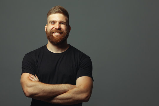 Fabulous at any age. Emotive portrait of laughing charismatic muscular 30-year-old man standing over light gray background. Perfect haircut. Rocker, biker, hipster style. Copy-space. Studio shot