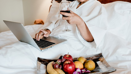 Picture of tourists used laptop and eating fruits on the bed, health food concept