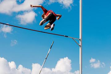 Fototapeta athlete passes bar in pole vault background blue sky and clouds obraz