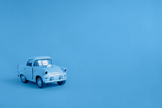 Blue toy car on the road on a classic blue color background