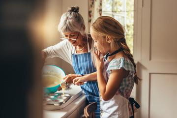 Granny and kid making cup cakes - fototapety na wymiar