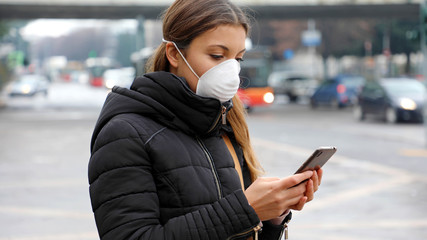 Young woman using smart phone in the city wearing face mask because of air pollution, particulates or flu virus, influenza, coronavirus