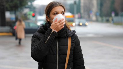 COVID-19 Pandemic Coronavirus Woman in city street wearing face mask protective for spreading of...