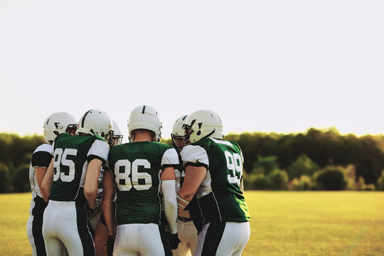 American football team in a huddle on a sports field