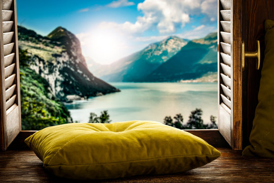 Wooden window sill background with pillows and free space for your decoration.Landscape of spring lake with mountains nad copy space