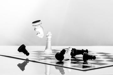 Spielfiguren auf einem Schachbrett fallen um