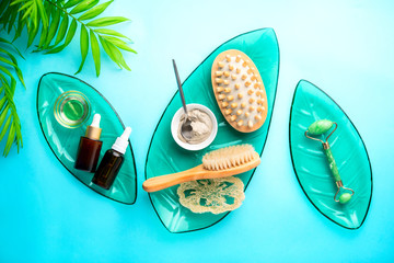 Spa setting background with cosmetic clay and jade roller