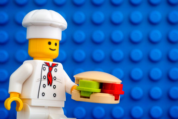 Tambov, Russian Federation - October 19, 2019 Lego chef minifigure with hamburger against blue baseplate background. Studio shot.