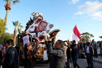 Supporters of Libyan National Army (LNA) commanded by Khalifa Haftar, hold a picture of Turkish President Tayyip Erdogan as they celebrate near a Turkish military armored vehicle, which LNA said they confiscated during Tripoli clashes, in Benghazi