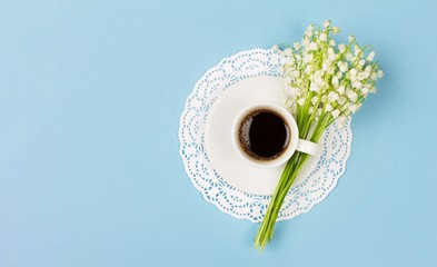 Wall Murals Lily of the valley cup of black coffee on a saucer and a bouquet of lily of the valley flowers on a blue background with copy space, top view flat lay