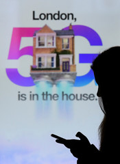 A woman walks past an advertisement promoting the 5G data network at a mobile phone store in London