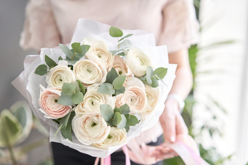 Persian buttercup in womans hands. Bunch pale pink ranunculus flowers with green eucalyptus. The work of the florist at a flower shop