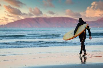 Lone surfer walks into the ocean at dawn in Pismo Beach