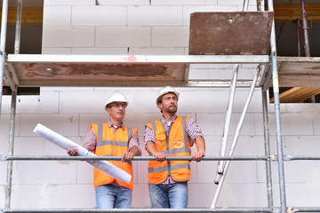 construction manager and architect on site during the construction of a house - planning and control on site - teamwork