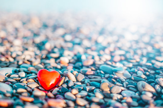 Romantic symbol of red heart on the pebble beach