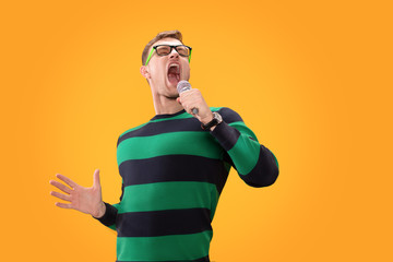 Young man in glasses singing song in microphone. Young posing isolated on yellow orange background. People lifestyle concept.