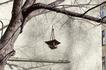 An empty feeding trough is hanging on a branch of a bare tree against the background of a stone wall of a house