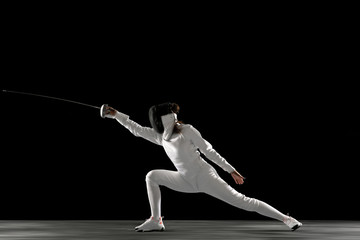 Catching moment. Teen girl in fencing costume with sword in hand isolated on black background....