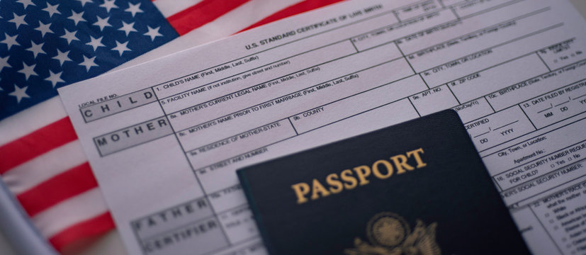 U.S. standard certificate of live birth application form next to American flag and Passport of USA. Wide photo. Birthright citizenship concept.
