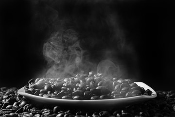 steaming coffee beans in a saucer on a black background