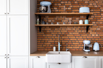 Kitchen in a contemporary shaker style with pastel blue kitchen appliances and orange cooker and the hood. Brick wall backsplash and retro style accessories. Shaker style kitchen.