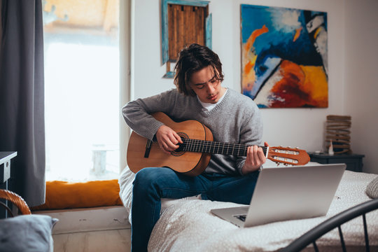 young man playing guitar in his room