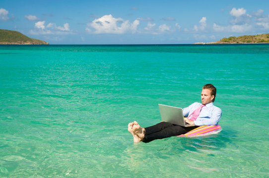 Barefoot businessman working on his laptop while floating on a colorful inflatable ring in bright tropical waters