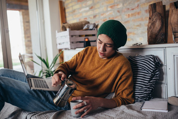young man using drinking coffee relaxed in sofa at his room