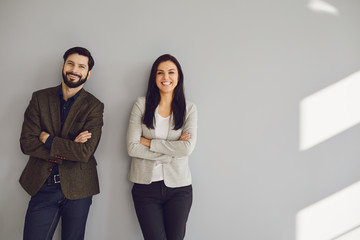 A businessman and a business woman are standing against a gray wall
