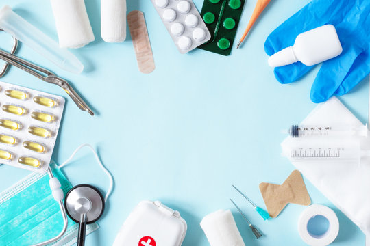 Medical equipments with stethoscope, scissors, syringes and other objects on blue background top view.