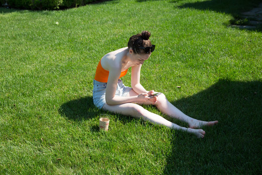 caucasian millennial female sitting on lawn looking at phone in shorts during summer in the sun and yard