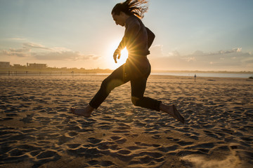 millennial guy running and dancing on beach during sunset
