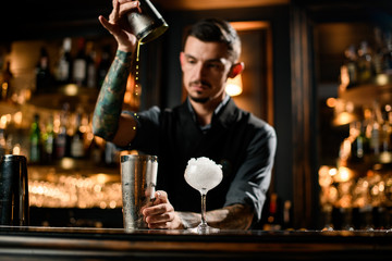 Photo sur Plexiglas Bar Male bartender cooking cocktail with special bar equipment