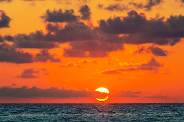 Dramatic sunrise over the ocean. Main color is lush lava, color of the year 2020. Beach of Cayo Santa