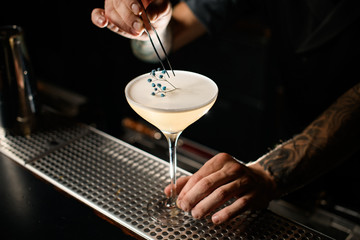 Close-up of bartender decorating cocktail with small branch